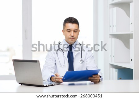 medicine, profession, technology and people concept - male doctor with clipboard and laptop computer in medical office - stock photo