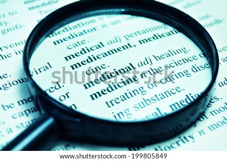 Medicine related words in the dictionary under magnifying glass - stock photo