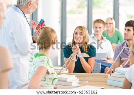 Medicine students with professor and heart anatomical model - stock photo