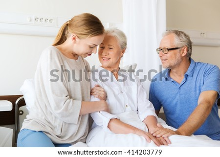 medicine, support, family health care and people concept - happy senior man and young woman visiting and cheering her grandmother lying in bed at hospital ward - stock photo