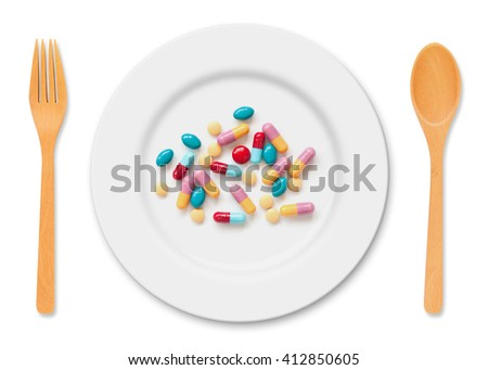 Medicine tablets and pills on white plate with spoon and fork on white background - stock photo