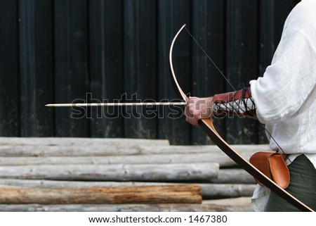 medieval Archer getting ready to shoot arrow at target - stock photo