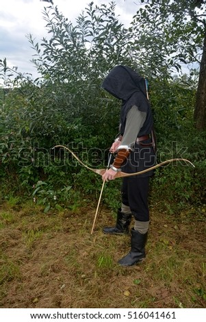 Medieval archer of the side stands with black hoodie and with tense curve and with arrow in the nature and looks down