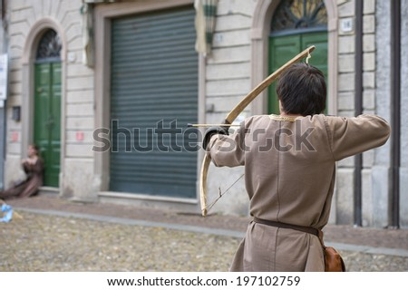 medieval archer while shooting a flying arrow  - stock photo