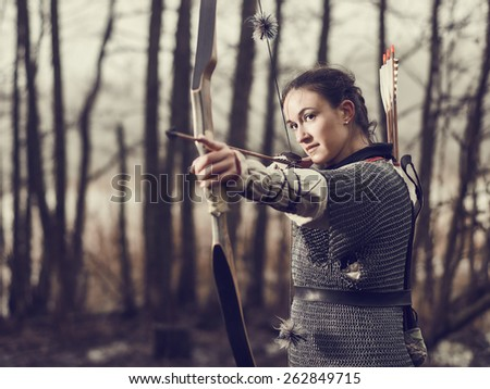 Medieval archer woman, she wearing a chainmail and use a bow and arrow, gloomy forest, cross-processed image. - stock photo