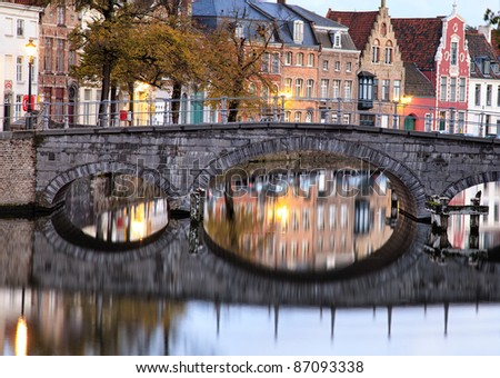 Medieval bridge over canal in Bruges, Belgium, in early morning skylight with quaint buildings reflected in the river - stock photo