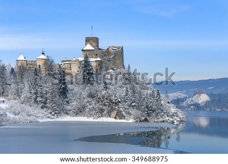 Medieval castle in Niedzica, Poland, in winter at partially frozen artificial Czorsztyn lake on Dunajec river and the far view of Czorsztyn castle - stock photo