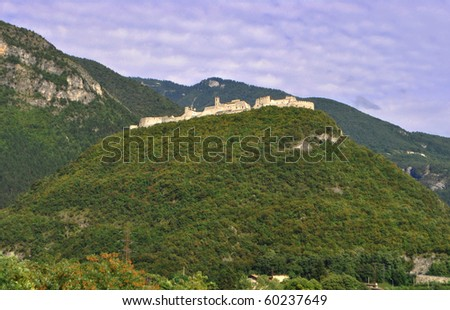 medieval castle in the hills of Trentino Italian queens self surrounded by dense vegetation and forests of larch and pine - stock photo