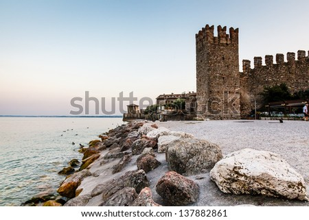 Medieval Castle on the Rocky Beach of Lake Garda in Sirmione, Northern Italy - stock photo