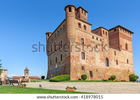 Medieval castle under blue sky in town of Grinzane Cavour, Piedmont, Northern Italy. - stock photo