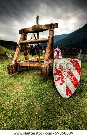 medieval catapult and shield - stock photo