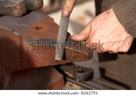 medieval craftsman blacksmith filing a piece of iron