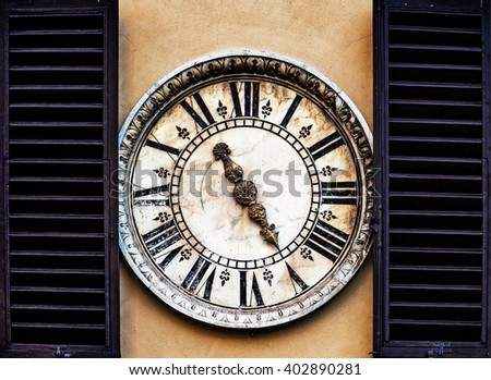 Medieval external wall clock  between window shutters in Florence, Italy  - stock photo