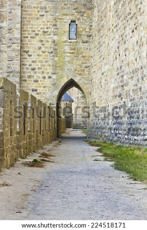 Medieval fortress wall and boundary with a window and gate on an empty path. - stock photo