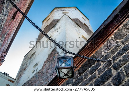 Medieval fortress walls, ancient lantern on the chain and blurred castle tower as a background - stock photo