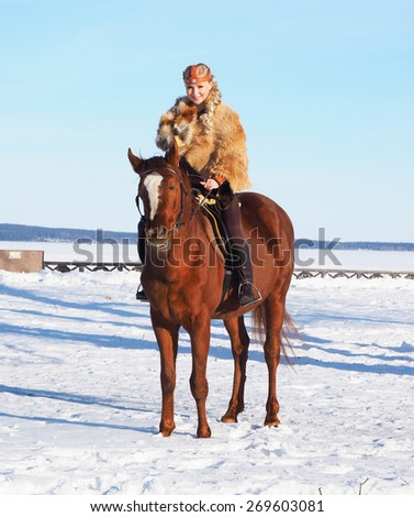 medieval girl on a horse by the lake in the winter - stock photo