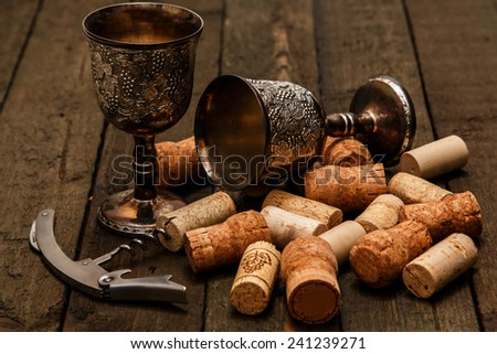 Medieval goblets and wine corks on wooden table