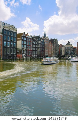 medieval houses and ships over water in Amsterdam, Netherlands