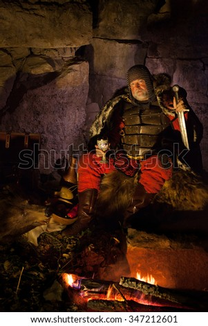 Medieval King in armor with the sword in one hand and wineglass in another is sitting on furs near the camp fire.