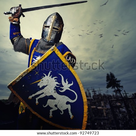Medieval knight against hill full of crosses. - stock photo