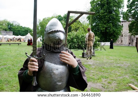 Medieval knight and dead body hanging from gallows in background - stock photo