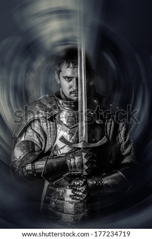 Medieval knight holding a sword - stock photo