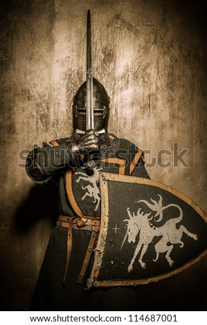 Medieval knight  holding sword in front of his face - stock photo