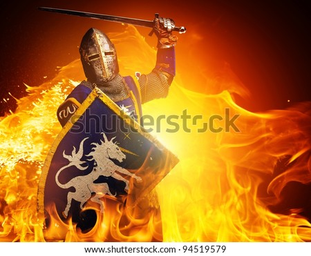 Medieval knight in attack position on fire background. - stock photo