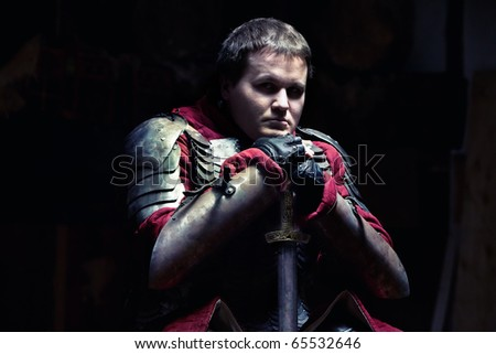 Medieval knight in the armor with the sword. - stock photo