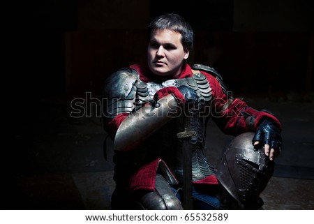 Medieval knight in the armor with the sword and helmet. - stock photo