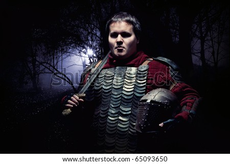 Medieval knight in the armor with the sword and helmet. Dark forest on the background. - stock photo