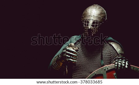 Medieval knight in the armor with the sword and shield. Artistic toning.