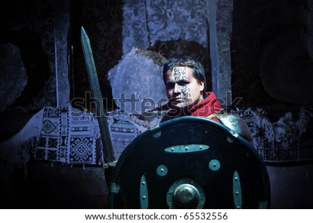 Medieval knight in the armor with the sword and shield. Portrait in the shadows. - stock photo