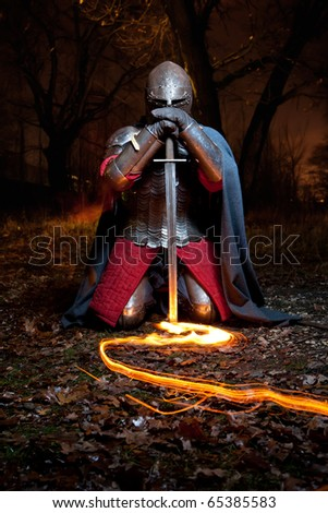 Medieval knight in the armor with the sword. Portrait in the forest. - stock photo