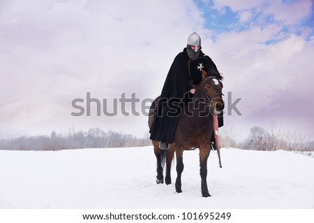 Medieval knight of St. John (Hospitallers) on a bay horses - stock photo