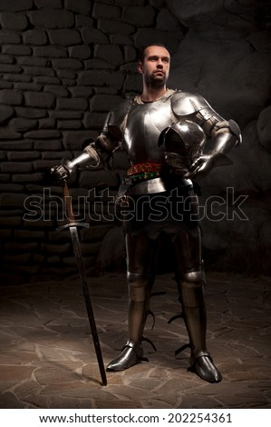 Medieval Knight posing with sword  and helmet in a dark stone background. Full-length portrait. - stock photo