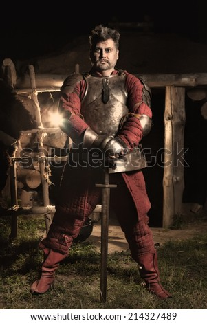 Medieval knight. Wooden house on the background. - stock photo