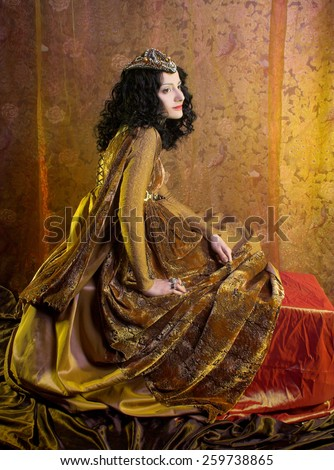 Medieval  lady. Portrait of young woman with dark curly hair in yellow dress.