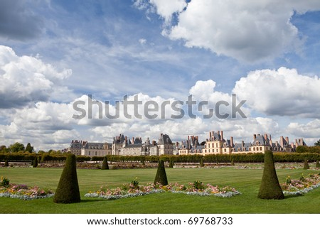 Medieval landmark royal hunting castle Fontainbleau near Paris in France and garden with flowers on the cloudy blue sky background - stock photo
