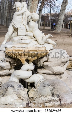 Medieval marble statue of two kids on fountain in European park