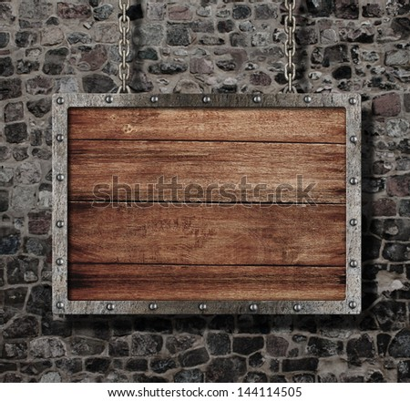 medieval old sign with chain on stone wall - stock photo