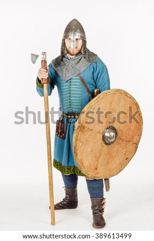 medieval slavic soldier looking at camera, with helmet, hauberks, spears, shields and axe, image on white studio background. historical concept. - stock photo