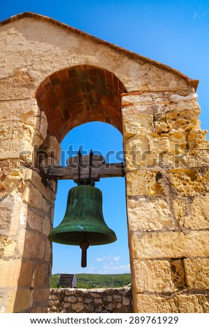 Medieval stone castle in Calafell town, Spain. Bell hanging in arch over blue sky background - stock photo