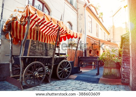 Medieval street and fragment of outdoors cafe in the old city of Riga, Latvia - stock photo