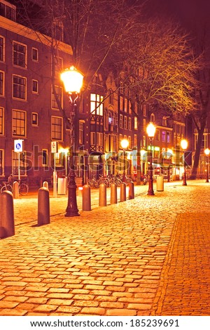 Medieval street in Amsterdam the Netherlands by night - stock photo