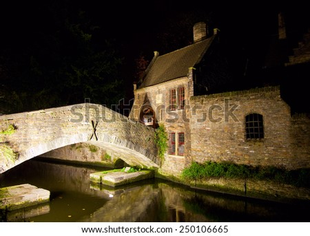 Medieval style houses illuminate at night by canal in Bruge, Belgium - stock photo