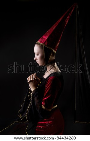 Medieval style portrait of a beautiful  woman in historical costume. low key. Looking down. Stage make up - stock photo