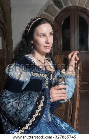Medieval style portrait of attractive woman in blue dress with wine glass in her hands - stock photo