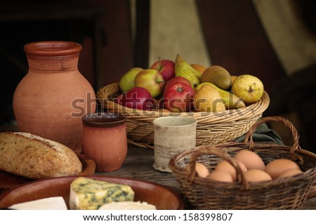 Medieval table setting with plates jugs beakers and baskets of apples and eggs & Medieval Table Setting Plates Jugs Beakers Stock Photo (Royalty Free ...