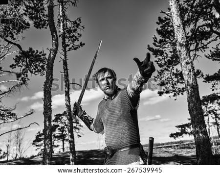 Medieval viking warrior wearing chainmail and he has the sword, north nature on background, black and white image
